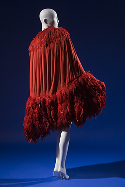 calf length evening cape in doubled red silk crepe de chine crinkled and smocked along curved edges of cocoon silhouette, crimson feather trim forming shawl collar and wide hem band